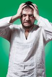 Funny bearded man with desperate expression. On green background Stock Images