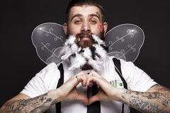 Funny bearded man with feathers and wings in the image of Cupid Valentine`s Day. royalty free stock photo