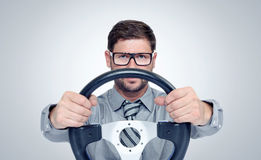 Funny bearded man in glasses with a steering wheel. On background Royalty Free Stock Photo