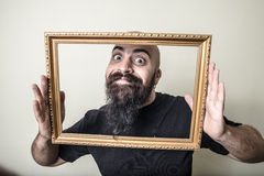 Funny bearded man with golden frame Stock Photo