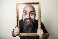 Funny bearded man with golden frame Royalty Free Stock Photography