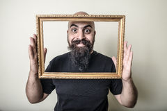 Funny bearded man with golden frame Stock Photos