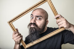 Funny bearded man with golden frame Royalty Free Stock Image