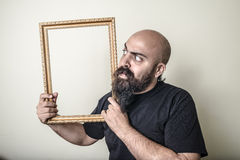 Funny bearded man with golden frame Royalty Free Stock Photos