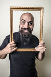 Funny bearded man with golden frame Stock Photography
