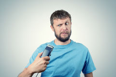 Funny bearded man with a hair-clipper. On background stock photography