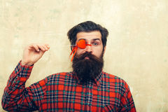 Funny bearded man holding red heart on stick before eye. Funny bearded man, caucasian hipster, with long beard and moustache in plaid shirt holding red heart on stock photography