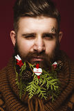 Funny bearded man in a New Year`s image as Santa Claus with decorations on his beard. Feast of Christmas. Royalty Free Stock Images