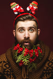 Funny bearded man in a New Year`s image as Santa Claus with decorations on his beard. Feast of Christmas. Royalty Free Stock Photography