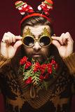 Funny bearded man in a New Year`s image as Santa Claus with decorations on his beard. Feast of Christmas. Royalty Free Stock Photo