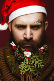 Funny bearded man in a New Year`s image as Santa Claus with decorations on his beard. Feast of Christmas. royalty free stock image