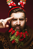 Funny bearded man in a New Year`s image as Santa Claus with decorations on his beard. Feast of Christmas. stock images