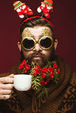 Funny bearded man in a New Year`s image as Santa Claus with decorations on his beard. Feast of Christmas. stock photos