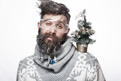 Funny bearded man in a New Year`s image with snow and decorations on his beard. Feast of Christmas. royalty free stock photography