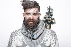 Funny bearded man in a New Year`s image with snow and decorations on his beard. Feast of Christmas. Photos shot in the studio royalty free stock photo