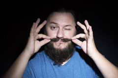 Funny bearded man touching mustache stock image