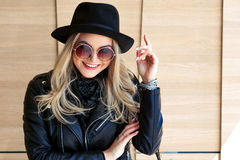 Funny and beautiful blonde in sun glasses and a hat. Trendy girl portrait outdoor. Happy smile Stock Photography