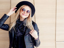 Funny and beautiful blonde in sun glasses and a hat. Trendy girl portrait outdoor. Holds hat Royalty Free Stock Image