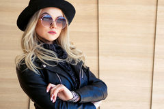 Funny and beautiful blonde in sun glasses and a hat. Trendy girl portrait outdoor. Holds hat. Funny and beautiful blonde in sun glasses and a hat. Trendy girl royalty free stock photo