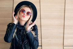 Funny and beautiful blonde in sun glasses and a hat. Trendy girl portrait outdoor. Kissing you Royalty Free Stock Image