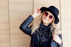 Funny and beautiful blonde in sun glasses and a hat. Trendy girl portrait outdoor. Laughs and holds hat Royalty Free Stock Images