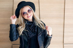 Funny and beautiful blonde in sun glasses and a hat. Trendy girl portrait outdoor. Laughs and holds hat Royalty Free Stock Photo