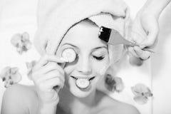 Funny beautiful girl having multi treatment spa. Black and white closeup image of funny girl beautiful blond young woman having multi treatment procedures happy Stock Photo