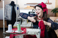 Funny beautiful happy smiling & looking at camera young pinup woman with sewing machine Royalty Free Stock Photography