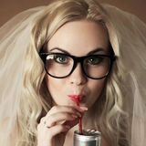 Funny beautiful hipster bride drinking something. Eyewear concept. portrait of a funny beautiful hipster bride drinking something from tin can through red royalty free stock images