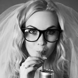 Funny beautiful hipster bride drinking something. Portrait of a funny beautiful hipster bride drinking something from tin can through plastic sipper. Daylight royalty free stock photography