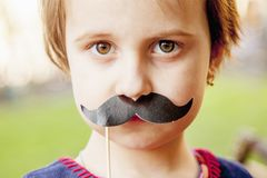 Funny beautiful little child girl wearing fake mustaches. Ready. For party stock photo