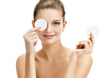 Funny beautiful model holding cotton pads up to her eyes. stock photos