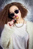 Funny beautiful sexy girl in glasses and a white coat licks a candy bar, bright makeup, fashion photography Studio Stock Images