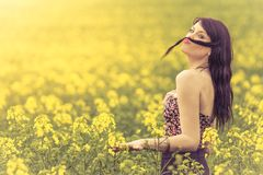 Funny beautiful spring girl with hair moustache in yellow meadow. Attractive happy young girl enjoying the warm summer sun and her health in a wide green and Stock Images