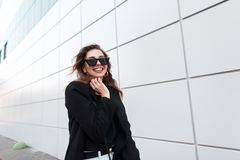 Funny beautiful young hipster woman in a black stylish coat in vintage white jeans in dark trendy sunglasses goes and laughs. Near a gray building in the spring royalty free stock photos