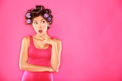 Funny beauty woman with hair rollers. Looking thinking to the side. Beautiful girl in pink on pink background. Multiracial Caucasian / Asian Chinese female hair Royalty Free Stock Photo