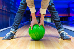 Beginner aiming to bowling pins. Funny beginner woman aiming to bowling pins stock image