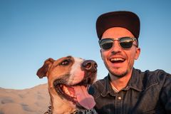 Funny best friends concept: human taking a selfie with dog. Happy young male person makes self portrait with his dog outdoors stock photos