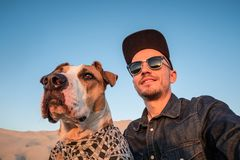 Funny best friends concept: human taking a selfie with dog. Young male person makes a spoiled self portrait with his dog outdoors stock photos