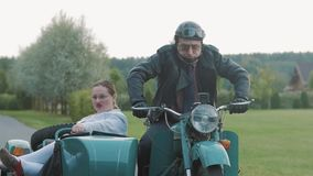 Funny biker ride motorcycle with woman nurse costume grimacing in sidecar stock video