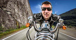 Funny Biker in sunglasses and leather jacket racing on mountain Stock Images
