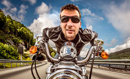 Funny Biker in sunglasses and leather jacket racing on mountain Royalty Free Stock Images