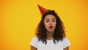 Funny biracial woman blowing party horn with effort celebrating birthday holiday. Stock footage stock video footage