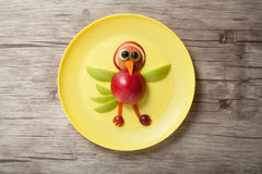 Funny bird made of apple. On plate and wooden background Stock Photography