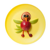 Funny bird made of apple. On yellow plate Stock Image