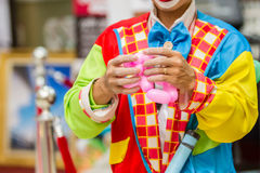 Funny birthday clown blows up a balloon. Royalty Free Stock Images