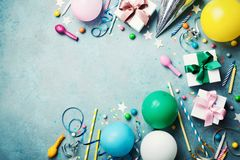 Funny birthday party background. Colorful balloon, gift box, confetti, candy and streamer on turquoise table top view. Flat lay. Funny birthday party background stock photography