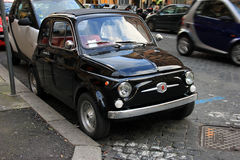 Funny black small old little italian car with round headlights a Stock Photography