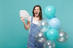 Funny blinking girl hold fan of money in dollar banknotes cash money celebrating with colorful air balloons isolated on stock image