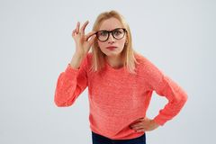 Funny blond in glasses staring at camera. Studio shot Stock Photography